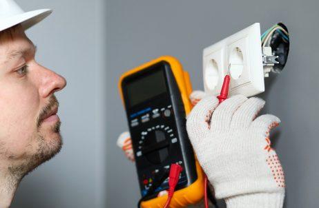 Homem medindo a voltagem da tomada.