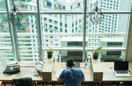 homem sentado em mesa de escritório sob iluminação de janelas altas